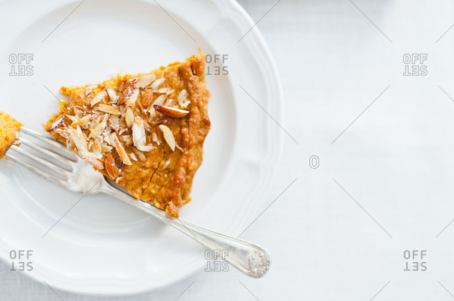 Overhead view of a piece of pumpkin pie with almonds