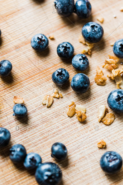 Blueberries and granola on wooden surface