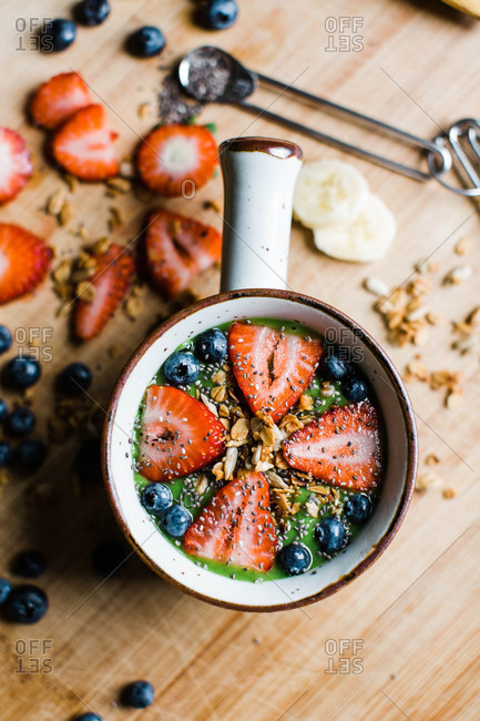Overhead view of a smoothie bowl with fruit, granola, and chia seeds