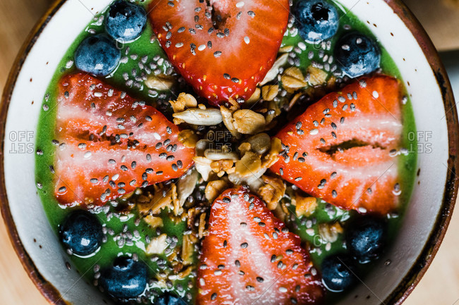 Top view of a smoothie bowl with fruit, granola, and chia seeds