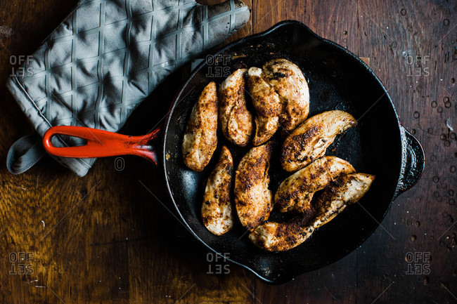 Chicken in a skillet on a wooden table