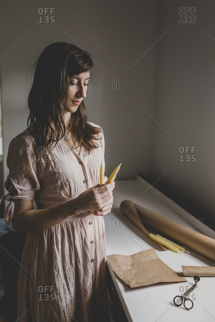 A brunette woman looks down at two beeswax pillar candles that she crafted