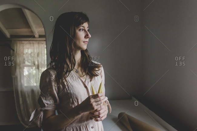 A brunette woman holding two beeswax pillar candles as she looks out a window