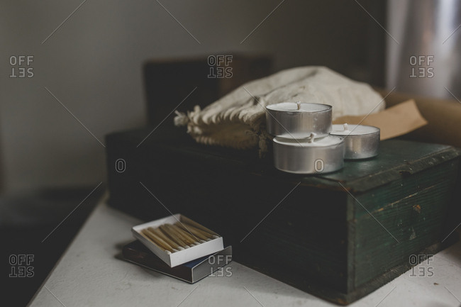 A set of tea light candles sits on a green wooden box with some matches nearby