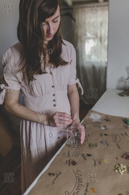 A young woman adds herbs to her intention candle that she is crafting
