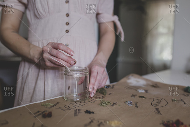 Young woman adds herbs to her intention candle that she is crafting