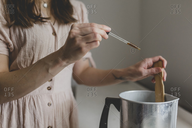 A brunette woman dropping essential oil scent to her wax for the candle she is making