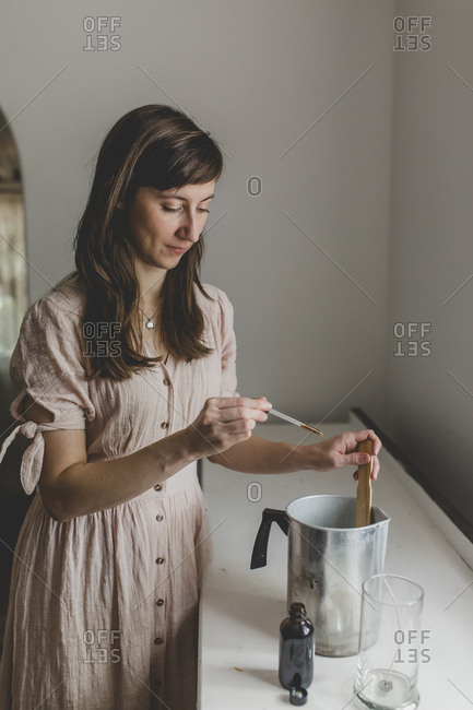 A brunette woman preparing to add essential oil scent to her wax for the candle she is making