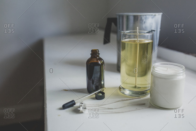 Crafting a wax candle with essential oil in an indoor workspace
