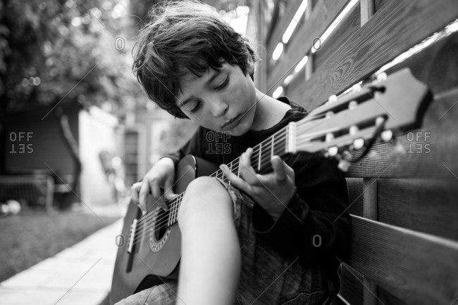 Boy playing guitar outside in the yard