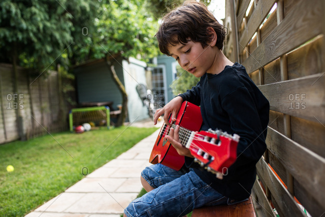 Boy playing guitar while sitting on a bench outside in the yard