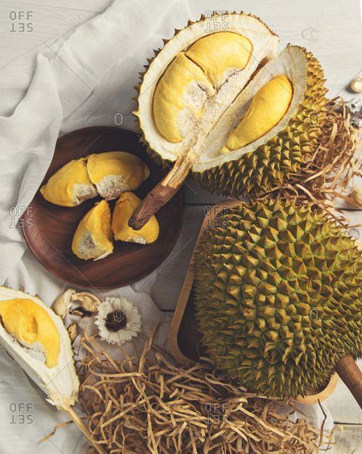 Whole and sliced durians with fruit served on plate