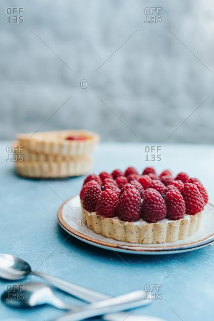 Raspberry tart on a blue table