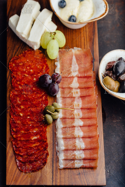 Slices of pork, ham and sausage on a wooden board with olives and grapes