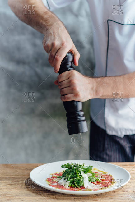 Chefs hands putting pepper on a beef Carpaccio
