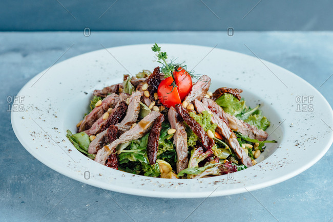 Beef salad in big white plate on blue table