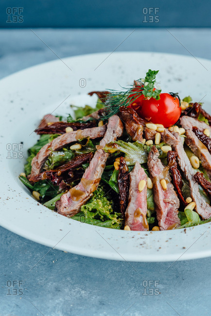 Close up of beef salad in big white plate on blue background