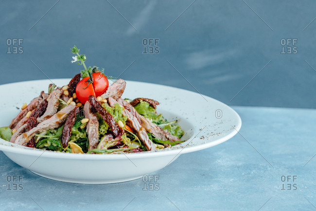 A beef salad in big white plate on blue table