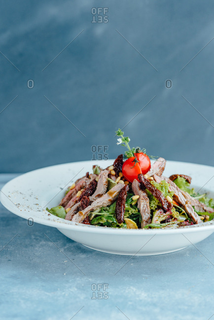 Close up of beef salad in big white plate on blue table