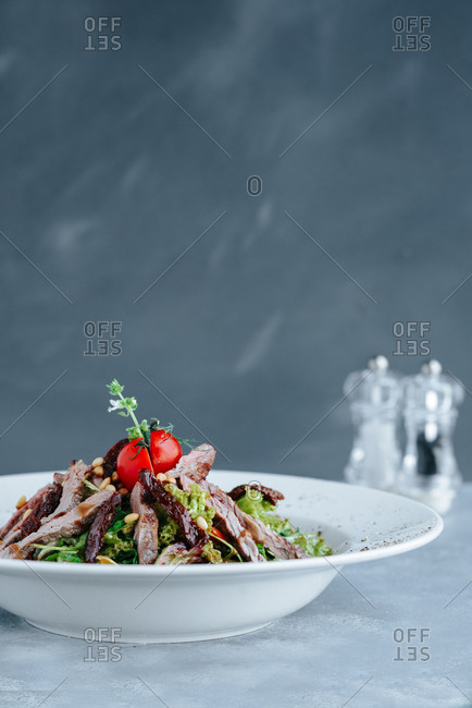 A beef salad in big white plate on gray background