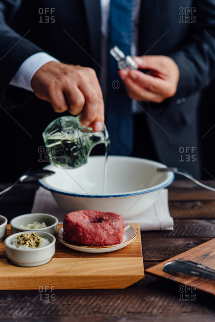 Man preparing beef tartare steak with ingredients next to him on table