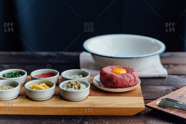 Beef tartare steak with all ingredients on table