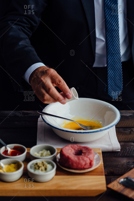 Man making beef tartare steak with ingredients next to him on table