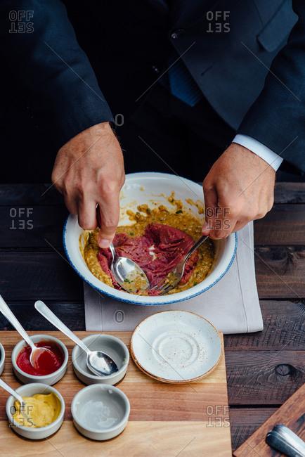 Man preparing beef tartare steak