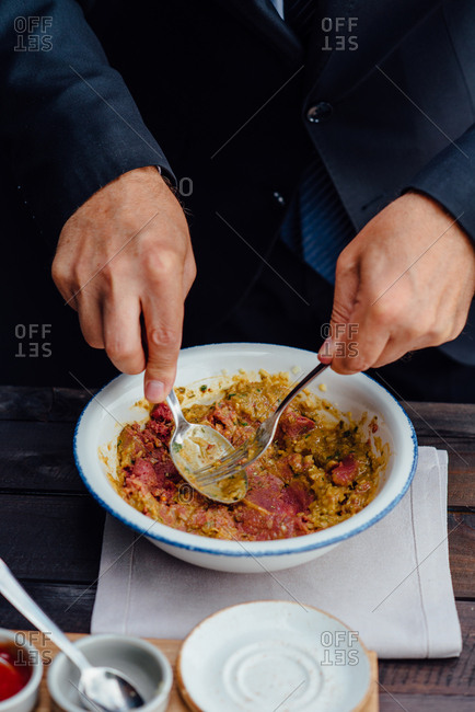 Man mixing beef tartare steak with ingredients