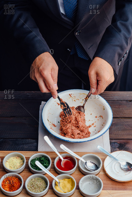 Overhead view of a chef mixing ingredients of a beef tartare steak dish