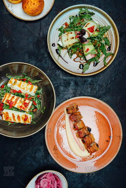 Plates with grilled cheese, zucchini and plums wrapped in bacon on dark background and cornbread