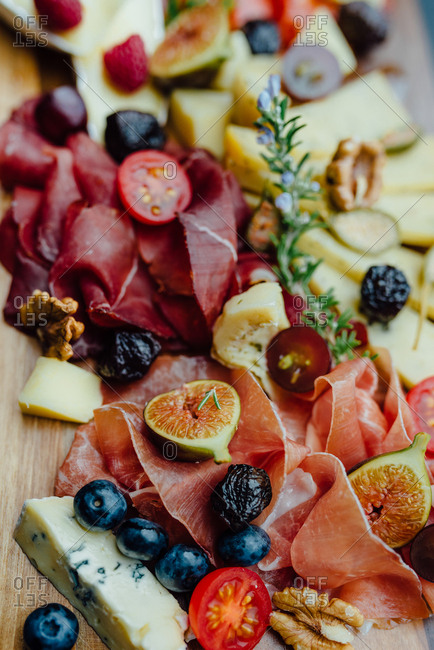 Close up of a board filled with pork, ham, sausage, cheese, figs, olives and tomato
