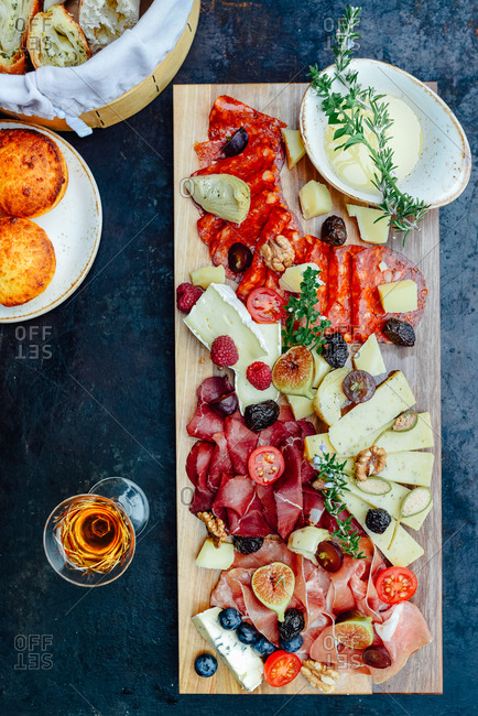 Wooden board filled with pork, ham, sausage, cheese, figs, olives and tomato