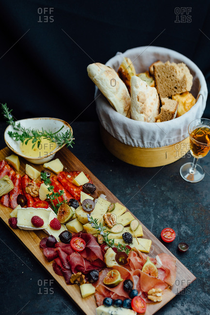 Wooden board filled with pork, ham, sausage, cheese, figs, olives and tomato served with bread