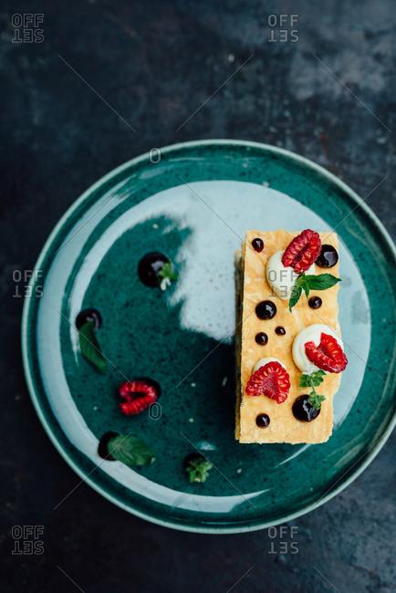 Overhead view of raspberry and vanilla cream layered cake on dark background