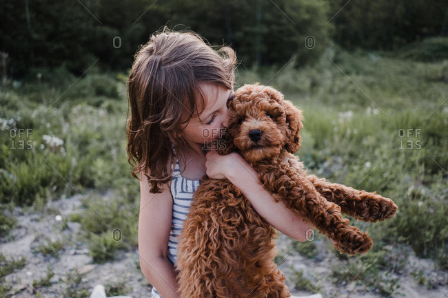 Girl kissing puppy in her arms