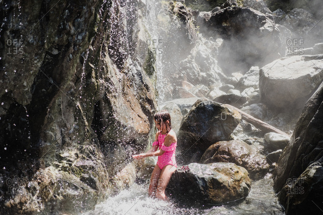Girl playing in waterfall, Tofino, Canada