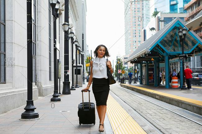 Businesswoman pulling luggage alongside train