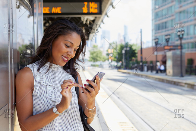 Businesswoman using cellphone in train station
