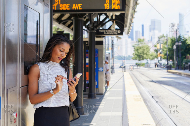 Businesswoman using cellphone by ticket machine