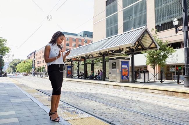 Businesswoman using cellphone in light rail station