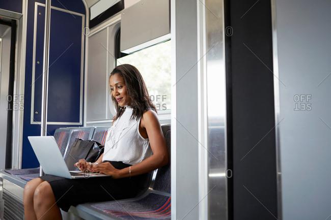 Businesswoman using laptop on train