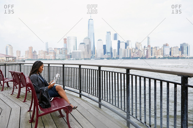 Businesswoman reading newspapers, New York City skyline in background