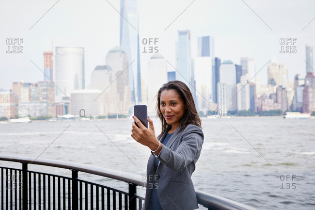 Businesswoman taking selfie, New York City skyline in background