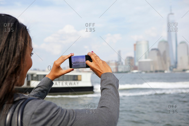 Businesswoman taking photograph of New York City skyline