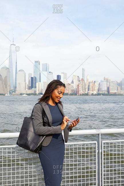 Businesswoman using cellphone, New York City skyline in background
