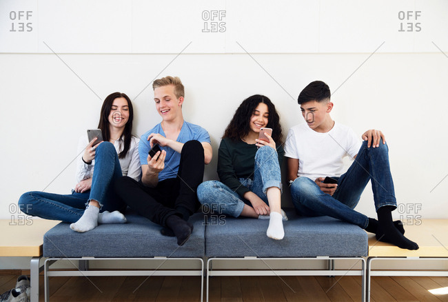 Four high school students on seating looking at smartphones
