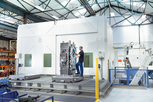 Apprentice engineer setting up large CNC machine in gearbox factory