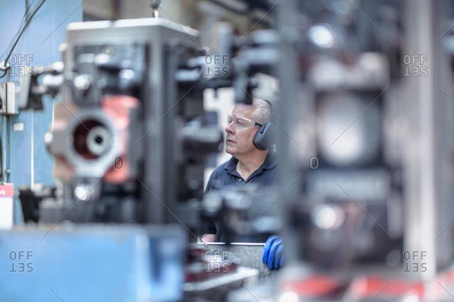 Engineer operating machine in gearbox factory