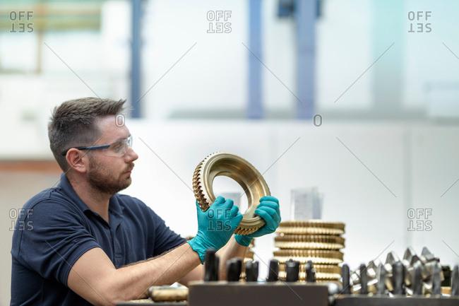 Engineer inspecting bronze parts in gearbox factory